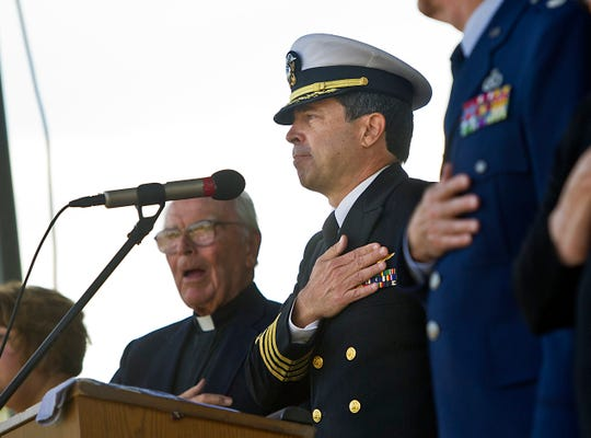 Eric Menger (center), a retired captain in the United States Navy, leads the audience in the Pledge of Allegiance during the 2013 Veterans Day ceremony in Vero Beach.