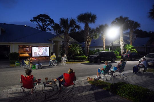 """As a way to stay in touch with friends and neighbors, Charlie Wilson, and his girlfriend Toddy Offutt, show 'My Cousin Vinny' from their driveway on Thursday, March 26, 2020, in the Pineapple Cay neighborhood in Indian River County. """"We'll show a different movie every night starting at 8 p.m. for whoever wants to come,"""" Wilson said."""