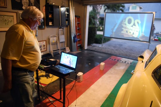 """Charlie Wilson sets up a projector in his garage on Thursday, March 26, 2020, to show a movie for his neighbors in their Pineapple Cay housing development in Indian River County. """"We're all cooped up in our houses all day, I thought this would be a fun way to get outside, talk with neighbors and have a few laughs,"""" Wilson said. """"Of course, we'll all be sitting six feet apart from each other, but hey, it's better than nothing."""" Wilson has dedicated himself to showing a movie every night for the foreseeable future."""