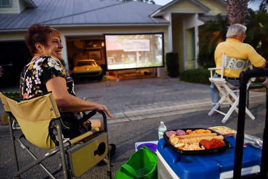 """Angie Moyer, a resident of the Pineapple Cay neighborhood in Indian River County, shares a laugh with friends and neighbors on Thursday, March 26, 2020, as she participates in a neighborhood movie night. Fellow resident, Charlie Wilson, decided to show a movie from his driveway as way to connect with his friends. """"You start to suffer from a little cabin fever,"""" said Moyer, """"and this is a way we can talk and check up on each other. It kind of brings back the old days of the drive-in,"""" Moyer added. """"Except now we have to use walkers,"""" Wilson said laughing."""