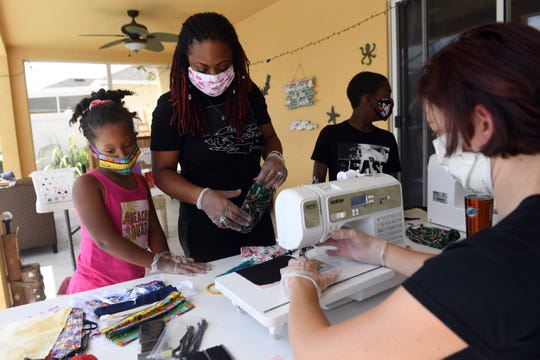 "Fashion designer Kallee Jackson (center) and her children Kallee, 9, and Arthur, 11, work with assistant, Jennifer Orazi on Friday, March 27, 2020, as they make face masks to be donated to local community organizations. ""I've not had much business since the coronavirus outbreak, so I decided to help fill a need in the community,"" Jackson said."