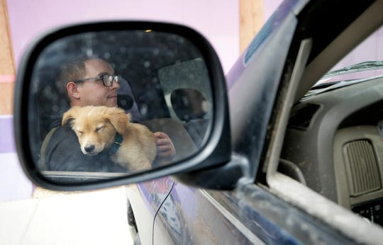 Cody Schultz holds his foster dog Milo in his truck as they wait in the parking lot for the dog to be treated by El Paso Animal Services staff. Animal Services is operating at a limited scale during the coronavirus pandemic.