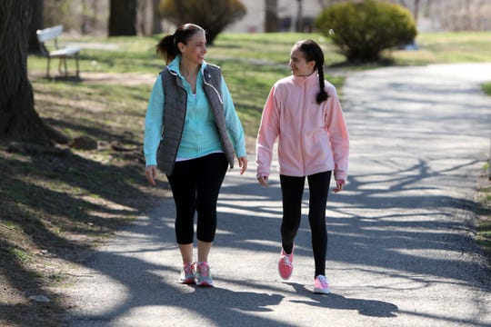 Jennifer Fox and her daughter Julia Casale, 15, during a walk at Nelson Park in Ossining, New York March 27, 2020. They've been going for walks or hikes for physical education class. Fox has been homeschooling her daughter, a high school freshman who has autism, with guidance from her teachers during the coronavirus pandemic. Fox is navigating this while doing her own job as an art teacher, virtually guiding her students in the Bronx.