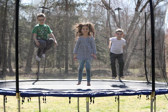Christopher Collins, 8, left, jumps on the trampoline with his sister Juliana, 5, and brother Dominic, 10, during a break from homeschooling amid the coronavirus pandemic in Yorktown Heights, New York March 27, 2020. Christopher, a third-grader who has autism, has additional challenges in homeschooling with the lack of related service providers. His mother, Jamie Collins, has taken this role on in addition to teaching three school curriculums and working full-time.