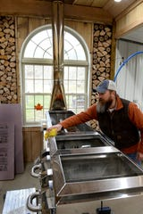 Chad Trent, co-owner of Hill 'n Hollow Family Farm and Sugarworks, cleans the evaporator before making a run of syrup.