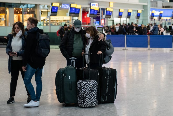 Airline passengers wearing face masks wait to check in their bags at London's Heathrow Terminal 5 departures as the outbreak of coronavirus intensifies on March 15, 2020 in London, England. U.S. President Donald Trump implemented a travel ban on European nations and extended it to include the United Kingdom and Ireland.