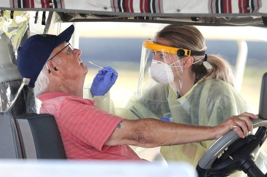 A resident of a long term care facility gets tested for the coronavirus with a nasal swab in The Villages, Florida, in March 2020.