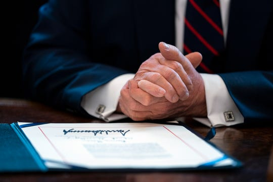 President Donald Trump finishes signing the coronavirus stimulus relief package in the Oval Office on Friday.