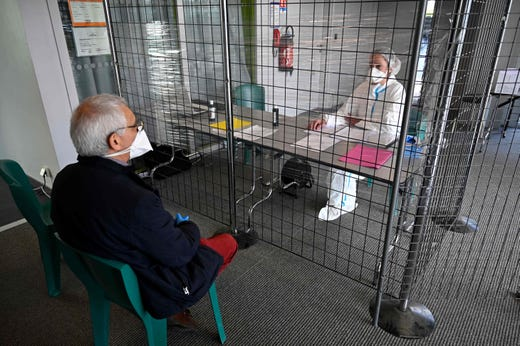 A doctor (L) shows the welcome desk of a consultation center dedicated to covid19 suspected patients in Tinteniac, France on March 27, 2020. The consultation center is located in an intermunicipal venue to remove patients at risk of infection from doctors' offices in order to continue caring for other patients.