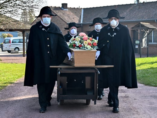 Members of the Charitable Brotherhood of Saint-Eloi de Bethune, each wearing a face mask, carry a coffin towards a grave, at Pierrette cemetery in Bethune, on March 27, 2020, as the country is under lockdown to stop the spread of the COVID-19 pandemic caused by the novel coronavirus.  Founded in 1188, the Charitables have for eight centuries taken care of funerals for the inhabitants of Bethune regardless of religion or wealth. Rarely, though, are they done behind almost-closed doors.