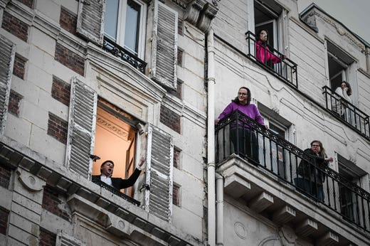 An opera tenor singer performs the song O sole mio from his window in Paris on March 26, 2020 on the evening of the tenth day of a strict lockdown in France aimed at curbing the spread of COVID-19, caused by the novel coronavirus.