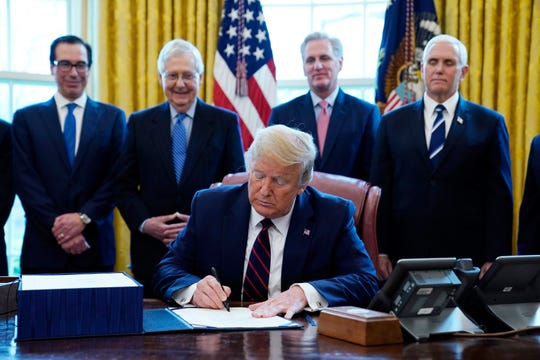 President Donald Trump signs the coronavirus stimulus relief package, at the White House on Friday.