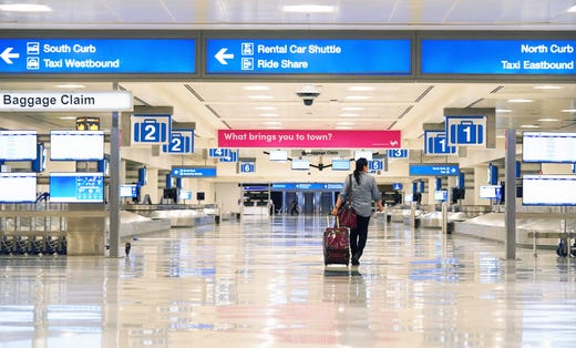 A lone traveler enters an empty baggage claim area in Terminal Four at Sky Harbor International Airport in Phoenix on Mar. 27, 2020. Airlines are reducing flights due to the coronavirus COVID-19 outbreak.