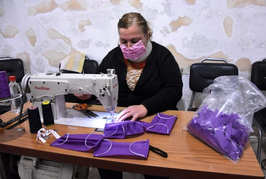 An Armenian Syrian volunteer sews masks to distribute to the poor for protection against the coronavirus pandemic, in Syria's northern city of Aleppo, on March 27, 2020.