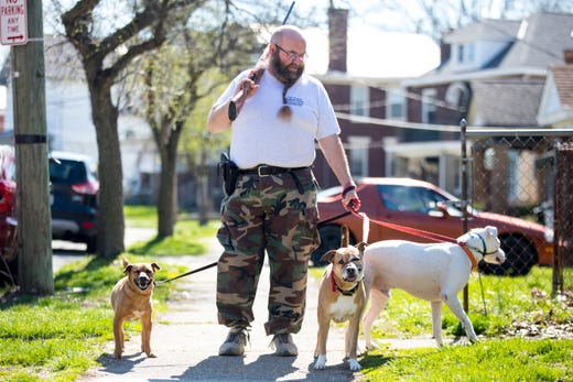 Robert Becker walks his dogs while carrying a .410 bore shotgun as a precaution due to the new coronavirus pandemic on March 26, 2020, in Cincinnati, Ohio.