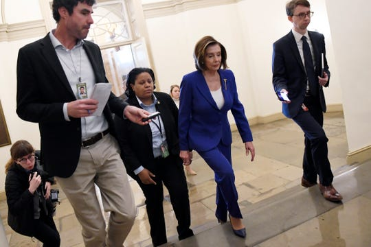 House Speaker Nancy Pelosi, D-Calif., is followed by reporters and staff as she arrives on Capitol Hill on  March 27, 2020.