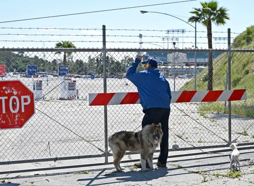 While on a walk with his dogs, a man looks through the locked gates at Dodger Stadium on Mar 26, 2020. Opening day between the San Francisco Giants and Los Angeles Dodgers was canceled due to the coronavirus pandemic.