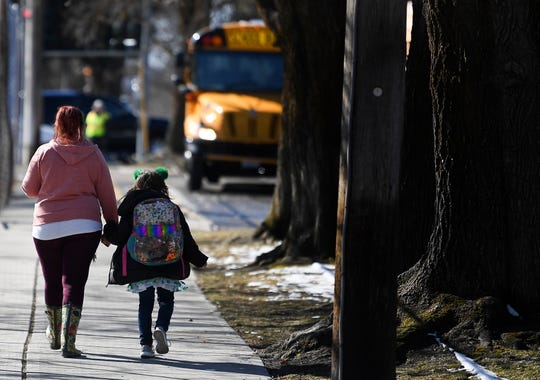 Samantha Green, left, walks her daughter Madison Green, a five-year-old kindergartner, to their car as school ends for the day Monday, March 16, 2020, at Roosevelt Elementary in Spokane, Washington. Officials said schools will be closed to help curb the spread of coronavirus.