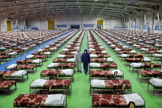 People in protective clothing walk past rows of beds at a temporary 2,000-bed hospital for COVID-19 coronavirus patients set up by the Iranian army at the international exhibition center in northern Tehran, Iran, on Thursday, March 26, 2020.