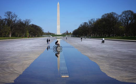A cyclist rides across the water remaining in the Reflecting Pool which has been drained for maintenance in Washington, DC on March 26, 2020.
