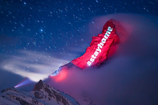 The iconic Matterhorn mountain is illuminated by Swiss light artist Gerry Hofstetter aiming to send messages of hope, support and solidarity to people suffering from the global coronavirus disease, COVID-19, pandemic in the alpine resort of Zermatt, Switzerland, Thursday, March 26, 2020.