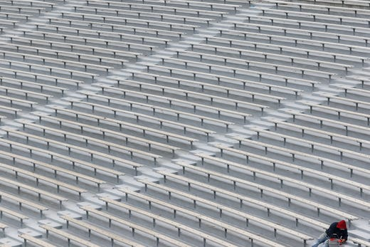 A man works on repainting surfaces in an empty Sanford Stadium in Athens, Georgia on Monday, March 16, 2020.