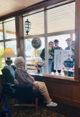Stafford Suites, an assisted living facility in Port Orchard, posted a photo on March 21 of a resident celebrating her birthday with family through the window.
