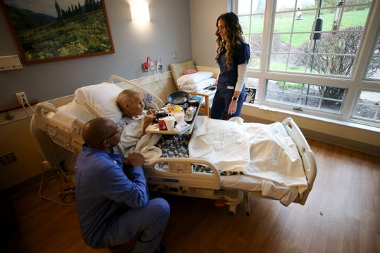 Amanda Anoai, a charge nurse at Hospice of Cincinnati Blue Ash, right, and Bernard Staples, a state-tested nursing assistant, cared for Frank Gilliland, 96, Friday, March 27, 2020, in Blue Ash, Ohio.