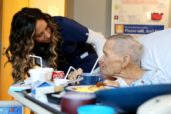 Mandy Anoai-Schall, a charge nurse at Hospice of Cincinnati Blue Ash, cares for Frank Gilliland, 96, Friday, March 27, 2020, in Blue Ash, Ohio.