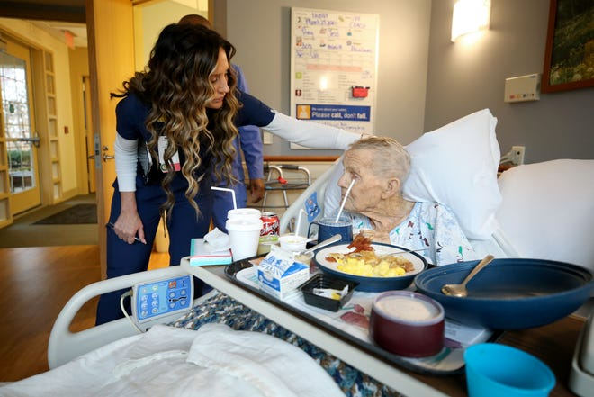 Amanda Anoai, a charge nurse at Hospice of Cincinnati Blue Ash, cares for Frank Gilliland, 96, Friday, March 27, 2020, in Blue Ash, Ohio.