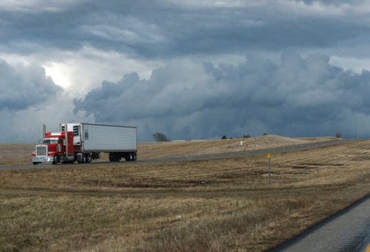 A semi truck rolls south on Highway 330 near Marshalltown Saturday as dark clouds loom in the background during a tornado warning in the area.
