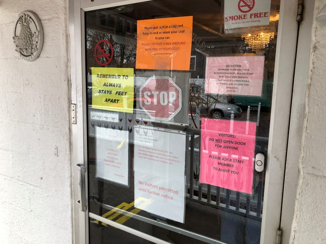 The glass door to the nursing home is covered in various warnings amid the coronavirus pandemic.