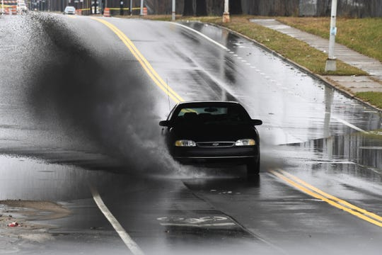 A motorist splashes through a flooded area along State Fair Avenue in Detroit on Saturday, March 28, 2020 after heavy rain.