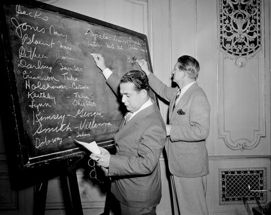 """In this April 18, 1943, file photo, Fred Mandel, foreground, president of the Detroit Lions, and Charles """"Chile"""" Walsh, assistant coach of the Cleveland Rams, look over prospects at the player draft of the NFL in Chicago."""