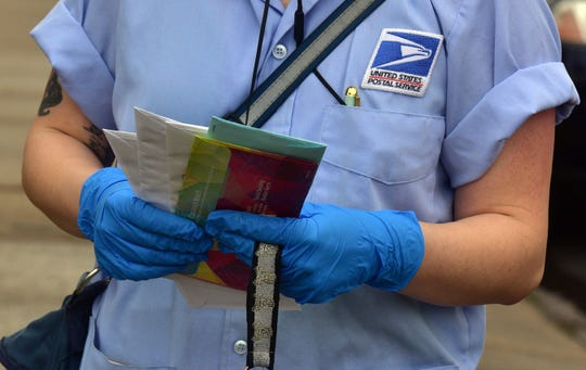 A U.S Postal Service mail carrier wears gloves while delivering mail in South Wilkes-Barre, Pa.