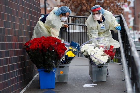 Emergency room nurses transport buckets of donated flowers up a ramp outside Elmhurst Hospital Center's emergency room, Saturday, March 28, 2020, in New York.