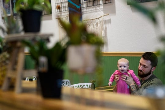 Nick Scott and 4-month-old Aurelia watch Brandie Scott, not pictured, prepare food as they spent time in the family's new restaurant Flourish Plant-Based Eatery located on the westside of Evansville, Thursday evening, March 26, 2020.