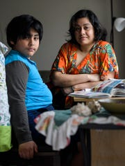 Mateo Baquerizo, 8, and his mother Wendy Araujo pose for a portrait while sitting at the desk where they work on his homeschool lessons at their Newburgh apartment, Friday, March 27, 2020. Araujo worked at Café Arazu in Newburgh but decided to cut her hours to stay home with her son when schools closed.