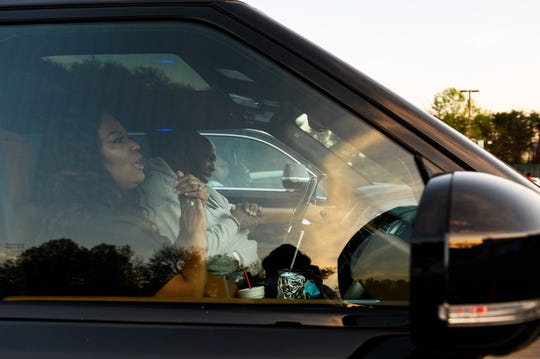 John and Aventer Gray sit in their vehicle during a drive-in service at Relentless Church Friday, March 27, 2020.