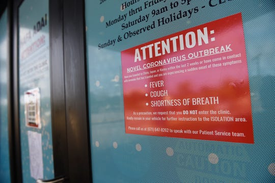 Patient warning signs are posted on the American Medical Center Mangilao entrance to prevent the spread of coronavirus, March 28, 2020.