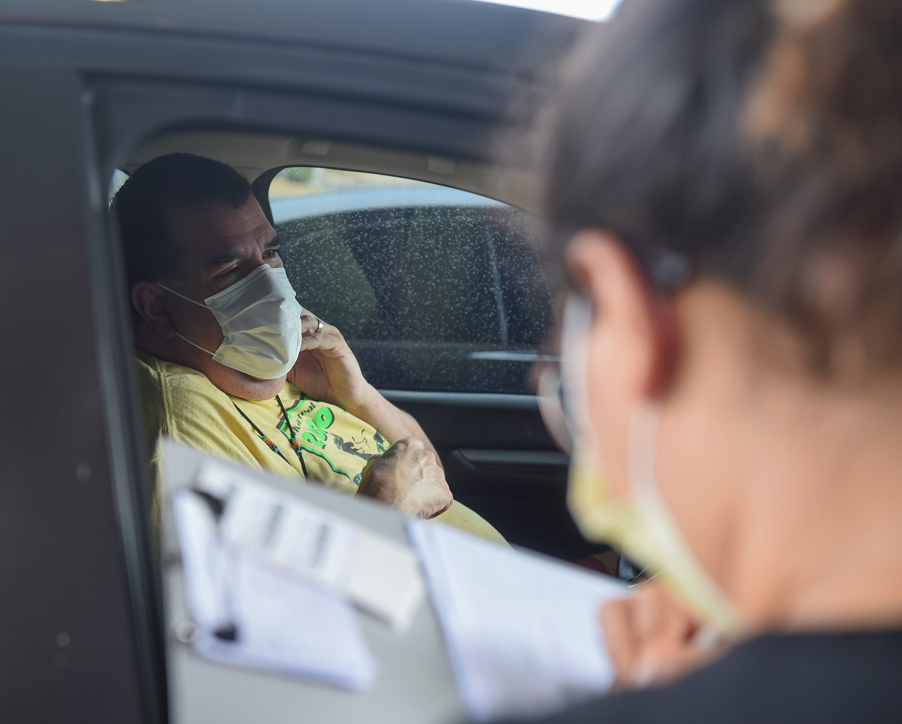 LouRayne Baza, an American Medical Center nurse lead, screens a patient at their drive-up service in Mangilao, March 28, 2020. American Medical Center employees have set up a drive-up screening service before processing, as a safety precaution in accordance with the governor's executive order, during the COVID-19 pandemic.