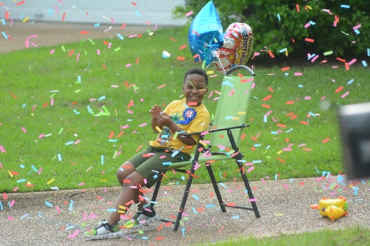John Michael Smith, who turned 7 on Saturday, closes his eyes as confetti floats around him. A parade of vehicles slowly drove by as occupants honked their horns and sang Happy Birthday to him as he sat in his birthday chair on March 28, 2020.