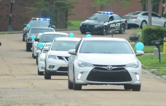 A procession of cars approaches the front yard of John Michael Smith to celebrate his seventh birthday on March 28, 2020. John Michael wasn't able to have a traditional birthday party due to social distancing guidelines over the coronavirus pandemic. So, his mother arranged neighbors and friends to drive by and wish him a Happy Birthday. The Clinton fire and police departments also showed up.