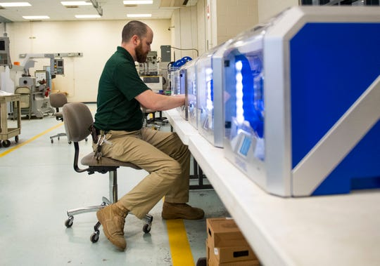 Tennessee College of Applied Technology tool and die instructor Robert Pepper removes a finished band from the 3D printer at Jackson State College in Jackson, Tenn., Tuesday, March 24, 2020.