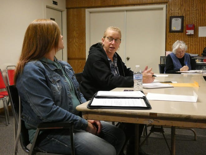 Morral Village Council Member Marjorie Moyer, center, asks an engineer about a planned road repaving project at the village's March meeting. Amber Belcher, left, sits next to her. The mayor and five of the six village council members are women.