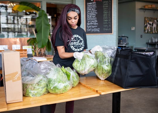 Tamboli's Pasta & Pizza employee Victree Hayes bags heads of lettuce for delivery in Memphis on Saturday, March 28, 2020. The restaurant is serving as a neighborhood grocery store in response to COVID-19.