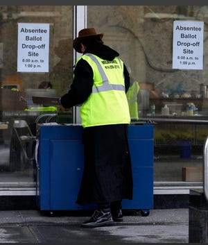 Jill Mickelson, Election Commission worker,checks the sealed ballot of a voter during drive-up early voting in the city of Milwaukee in March, ahead of the April election. Mayor Tom Barrett hopes to have in-person voting sites accessible to all 15 districts up and running ahead of the August and November elections.