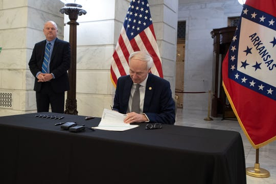 Gov. Asa Hutchinson signs legislation early Saturday morning creating a $173 million COVID-19 emergency fund for the state.