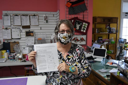 Judy Mahaney, owner of the Remember Me Quilt Shop, holds a sheet of instructions for a creating a face mask while wearing a mask that she sewed herself.