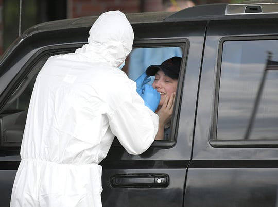 The Tennessee National Guard member performs a COVID-19 test on Frankie Rich at the drive-thru testing site at Putnam County Health Department in Cookeville on March 27.